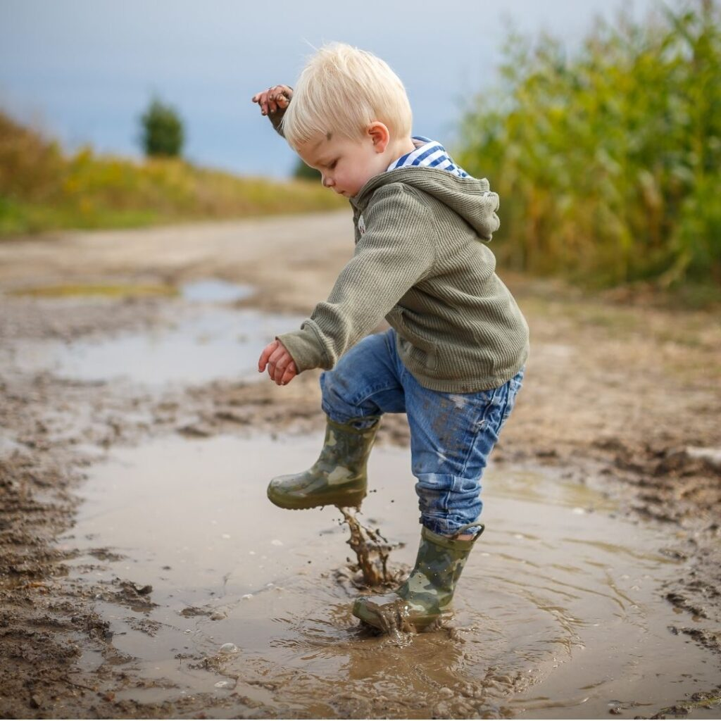 A toddler getting their clothes muddy